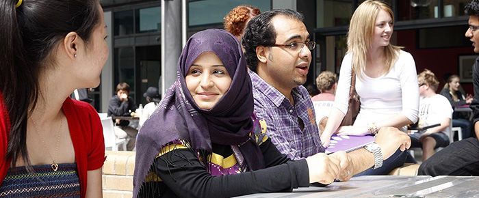 Male and female Arabic students smiling whilst talking in front of cafe